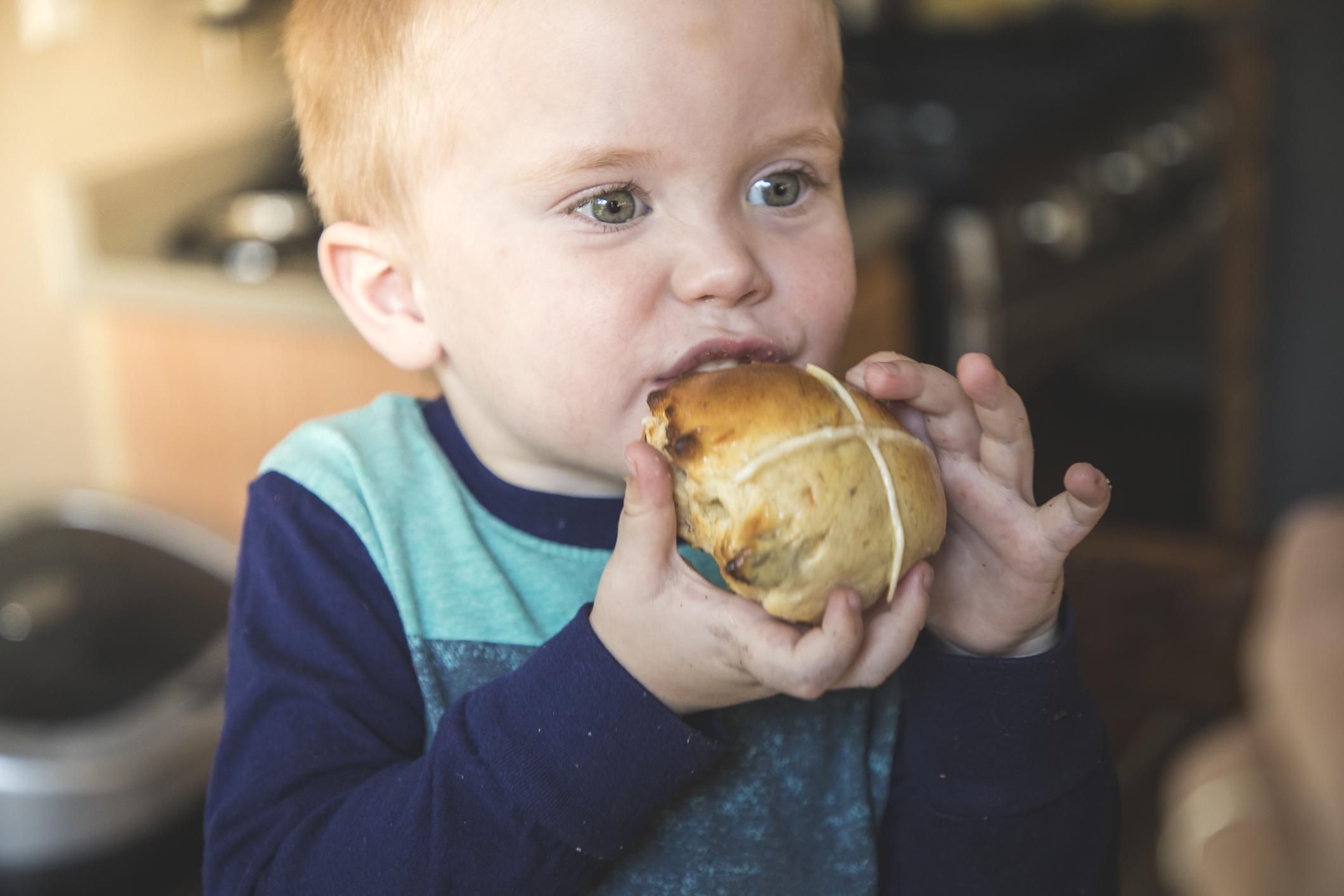 Child eating a Hot Cross Bun